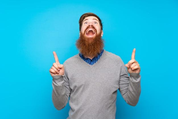 Uomo di redhead con la barba lunga sopra il blu isolato sorpreso e rivolto verso l'alto