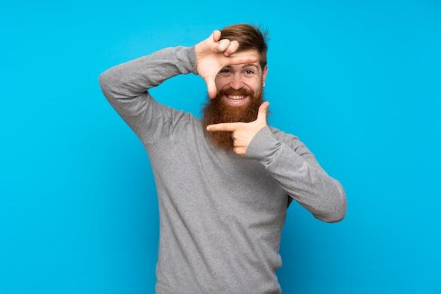Uomo di redhead con la barba lunga sul viso di messa a fuoco blu isolato. simbolo di inquadratura