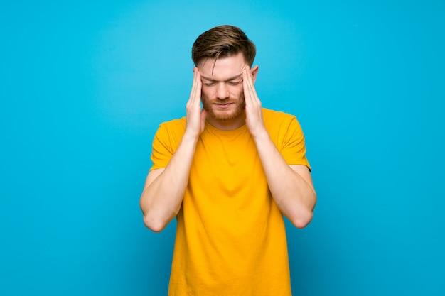 Uomo di redhead sul muro blu con mal di testa