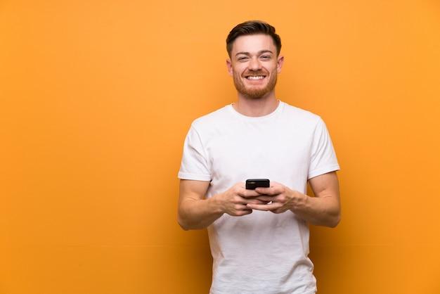 Uomo di redhead sul muro marrone inviando un messaggio con il cellulare