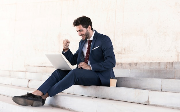 Uomo di seduta della foto a figura intera che esprime vittoria