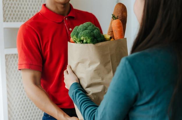 Uomo di servizio di consegna cibo intelligente in uniforme rossa consegna cibo fresco al destinatario e cliente giovane donna che riceve ordine dal corriere a casa, consegna espressa, consegna di cibo, concetto di shopping online
