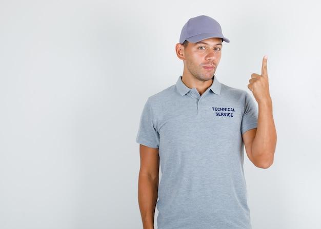 Uomo di servizio tecnico che mostra il dito in su in maglietta grigia con cappuccio