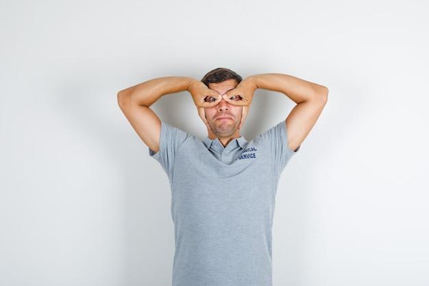 Uomo di servizio tecnico che mostra il gesto di occhiali in maglietta grigia e che sembra divertente