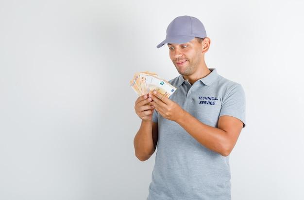 Uomo di servizio tecnico che tiene le banconote in euro in maglietta grigia con cappuccio e che sembra felice