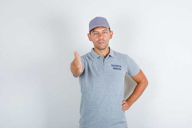 Uomo di servizio tecnico in maglietta grigia con cappuccio che dà la mano per la stretta di mano