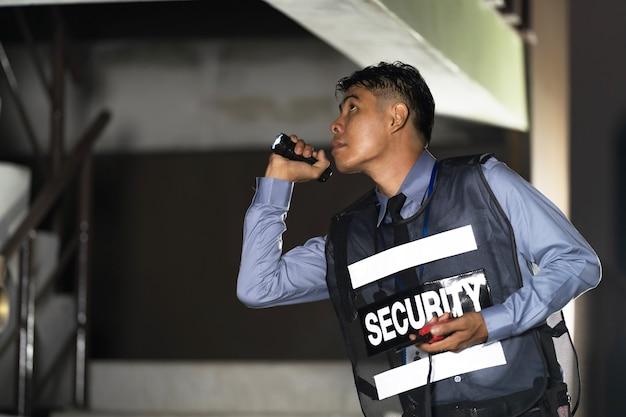 Uomo di sicurezza che sta all'aperto con la torcia elettrica in costruzione