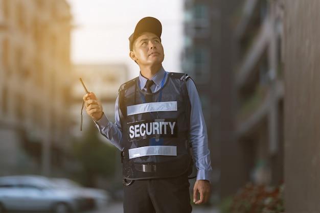 Uomo di sicurezza che sta all'aperto facendo uso della radio portatile