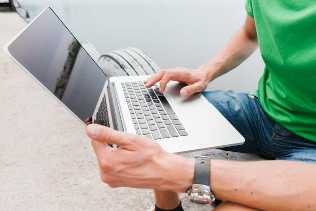 Uomo di sideview che lavora al computer portatile