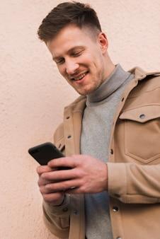 Uomo di smiley che esamina smartphone