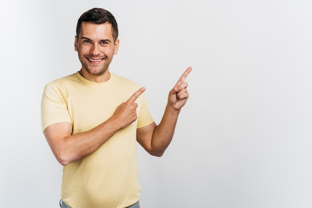 Uomo di smiley che indica in uno spazio della copia di direzione