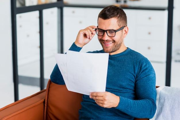 Uomo di smiley che legge a casa i documenti