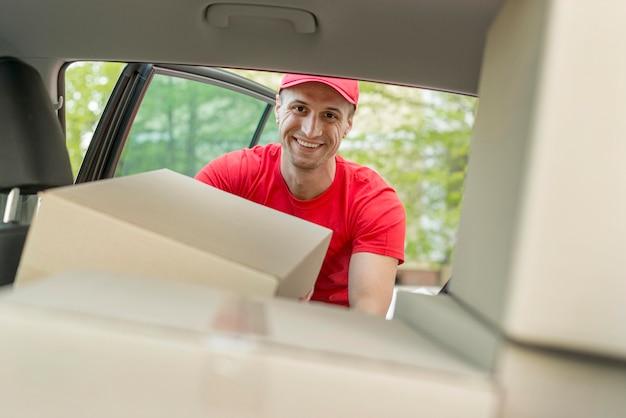 Uomo di smiley che mette pacchetto in automobile