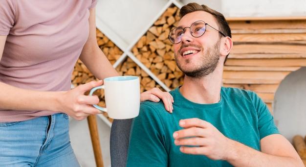 Uomo di smiley che ottiene il caffè in tazza