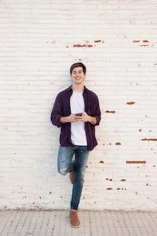 Uomo di smiley che propone mentre si tiene smartphone