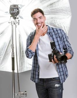 Uomo di smiley che tiene una macchina fotografica professionale