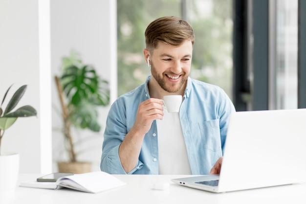 Uomo di smiley con airpods che lavora al computer portatile
