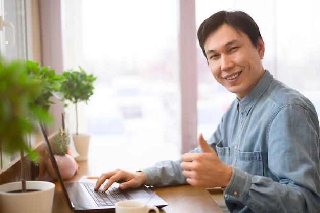 Uomo di smiley con il computer portatile che mostra segno giusto