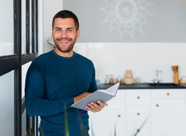 Uomo di smiley con il libro che guarda l'obbiettivo