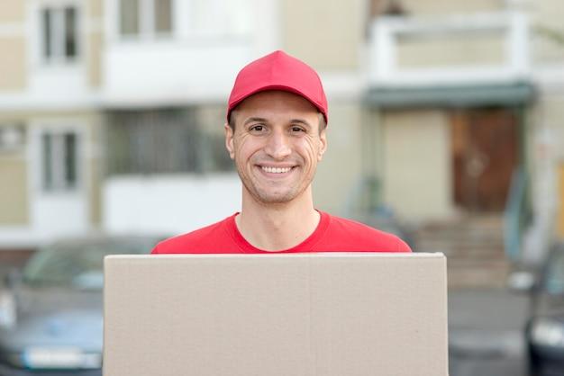 Uomo di smiley consegna pacchetto