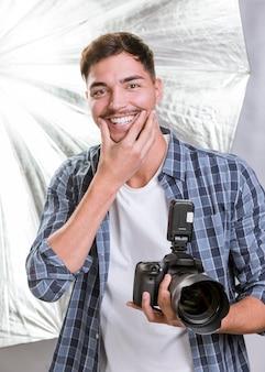 Uomo di smiley del colpo medio che tiene una macchina fotografica professionale