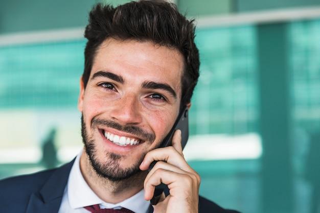 Uomo di smiley del primo piano che parla al telefono