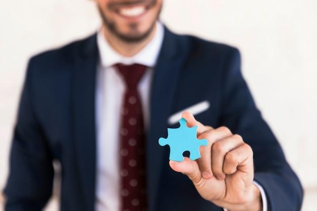 Uomo di smiley del primo piano che tiene un pezzo di puzzle