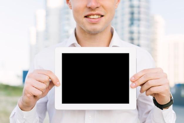 Uomo di smiley del primo piano con il modello della compressa