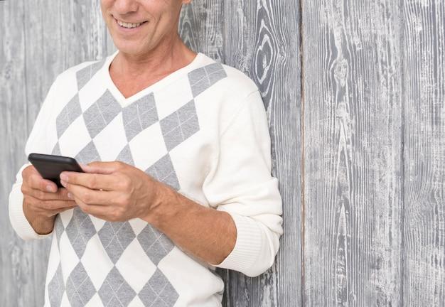 Uomo di smiley del primo piano con lo smartphone e il fondo di legno