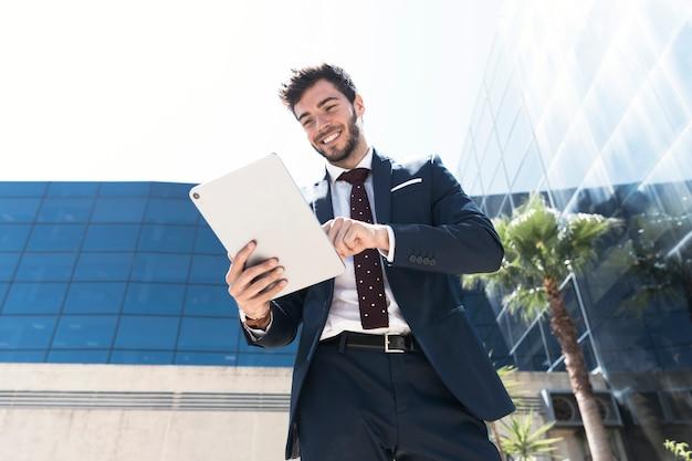 Uomo di smiley di angolo basso con il suo tablet