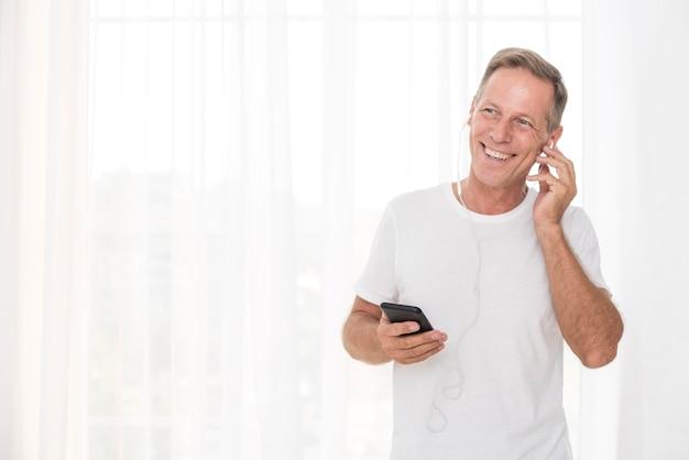 Uomo di smiley di tiro medio con smartphone e cuffie