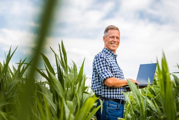 Uomo di smiley di vista di angolo basso con un computer portatile
