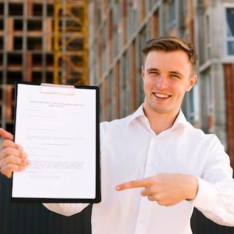 Uomo di smiley di vista frontale che indica al contratto