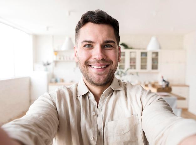 Uomo di smiley di vista frontale che prende selfie