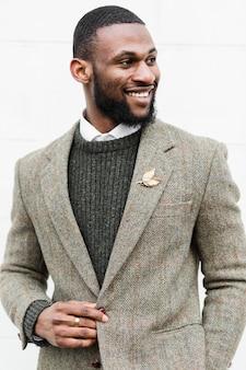 Uomo di smiley di vista frontale che propone in vestiti convenzionali