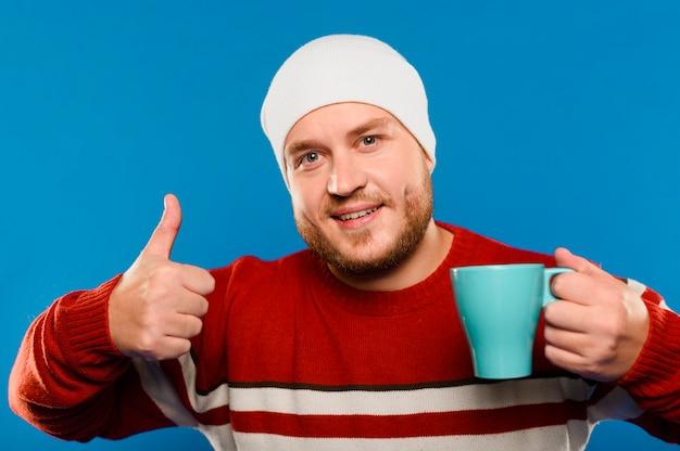 Uomo di smiley di vista frontale che tiene una tazza di caffè