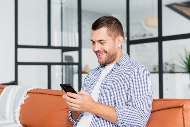 Uomo di smiley di vista frontale con lo smartphone