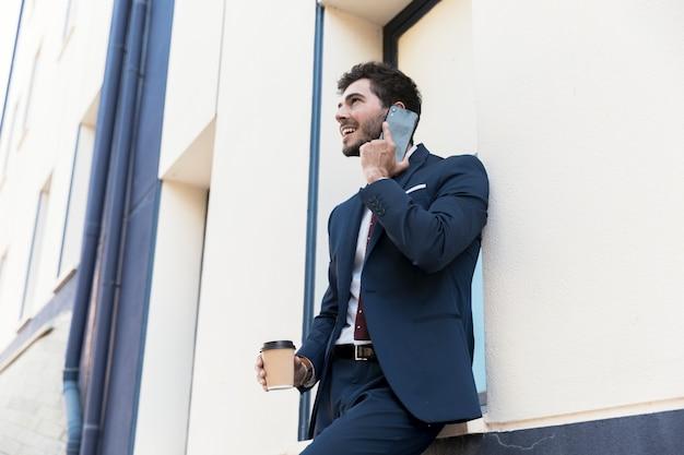 Uomo di smiley di vista laterale che parla al telefono