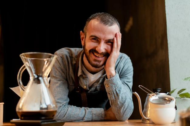 Uomo di smiley in grembiule in posa accanto alla caffettiera