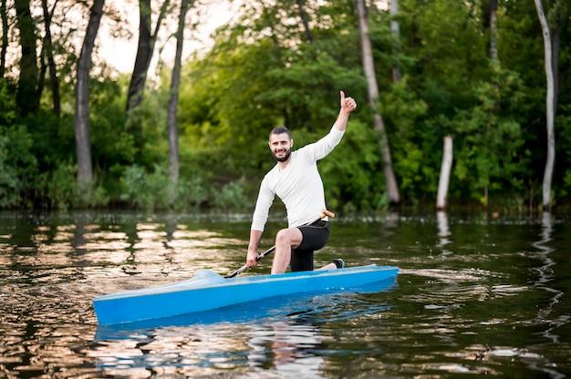 Uomo di smiley in kayak che mostra approvazione