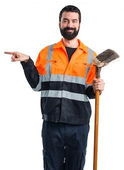 Uomo di spazzatura che punta verso il laterale