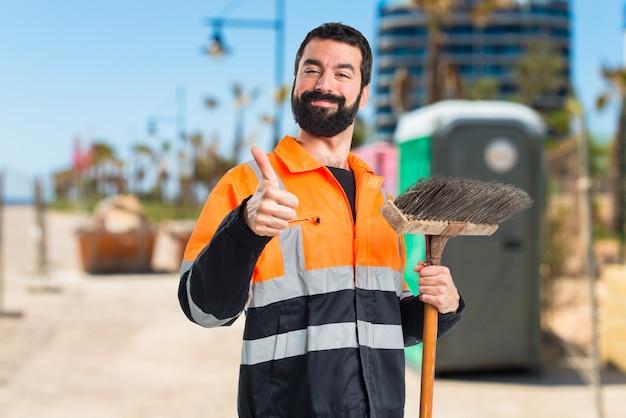Uomo di spazzatura con il pollice in su