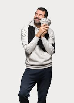 Uomo di sport che prende molti soldi sopra fondo grigio isolato