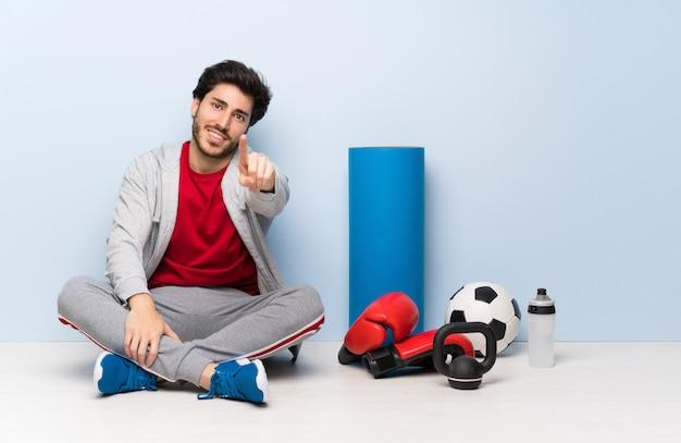 Uomo di sport che si siede sul pavimento che mostra e che alza un dito