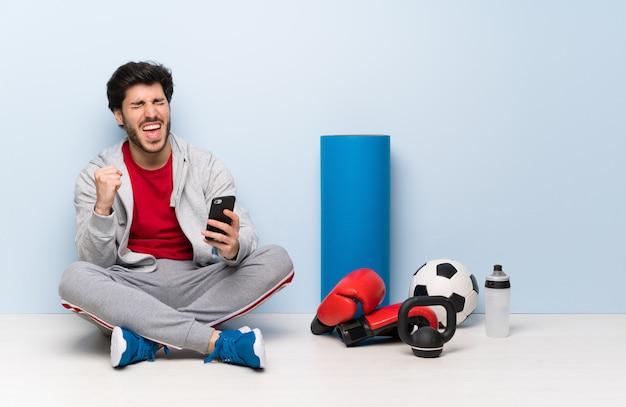 Uomo di sport che si siede sul pavimento con il telefono nella posizione di vittoria
