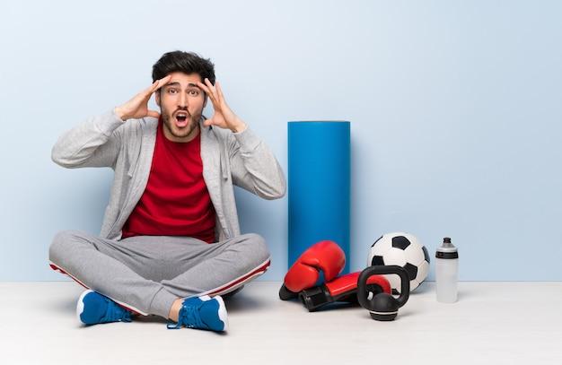 Uomo di sport che si siede sul pavimento con l'espressione sorpresa