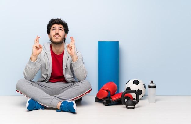 Uomo di sport che si siede sul pavimento con le dita che attraversano e che desiderano il meglio