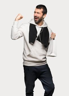 Uomo di sport che tiene molti sacchetti della spesa nella posizione di vittoria sopra fondo grigio isolato