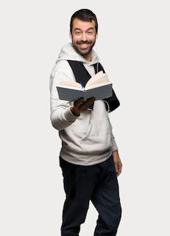 Uomo di sport che tiene un libro e dandogli a qualcuno sopra fondo grigio isolato