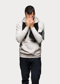Uomo di sport con espressione stanco e malato sopra fondo grigio isolato